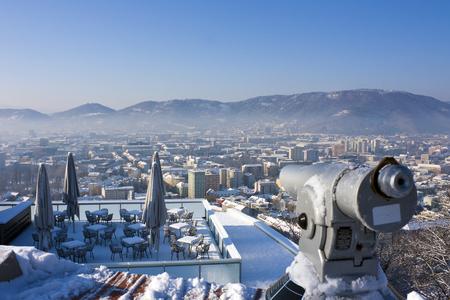 Telescope and terrace of restaurant in winter over snowy Graz, Austria, Europe