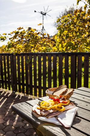 Brettljause, traditional wooden plate with cold cuts only with self-made food on terrace in vineyard on western Styria vine route