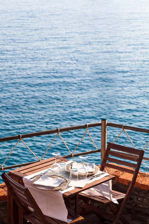 Wooden table with white, dishwater and chairs on ocean in a restaurant in Italy, Europe