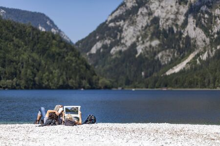 Couple reading book and newspaper on lake Leopoldsteiner near Eisenerz in Styria, Austria Stock Photo