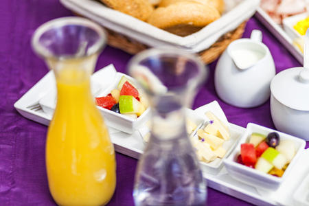 breadbasket: Fresh Breakfast or brunch with ham, eggs, bread, yogurt, fruits and coffee on violet table and white dishware