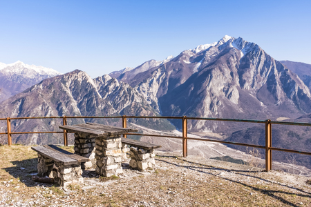 Wooden table and bench on Monte San Simeone with beautiful view to Monte Chiampon Stock Photo