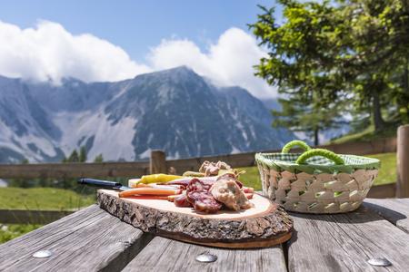 Brettljause on wooden table on Klagenfurter Hütte with view to mountain Weinasch in Karawanks