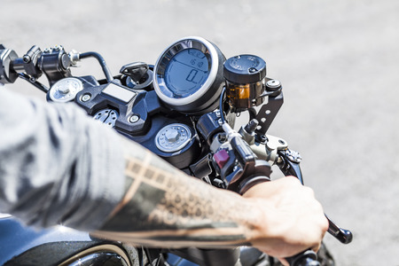 Cool looking tattoos on arms of motorcycle rider on custom made scrambler style cafe racer
