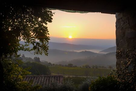 View from a terrace to a sunrise over foggy hills in the vineyards in Castellina in Chianti in Italy