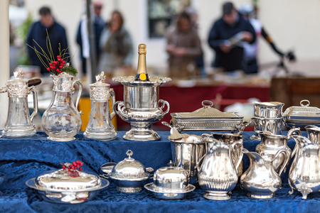 Champagne cooler and other silverware on flea market with people in the background Stock Photo