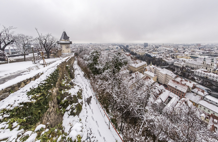 Landmark Uhrturm on hill Schlossberg in Graz on a snowy winterday