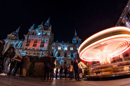 Spinning carousel on christmas fair on main square in Graz with town hall Stock Photo
