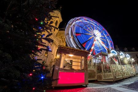 Ferris wheel on christmas fair on Mariahilferplatz in Graz with church Mariahilf