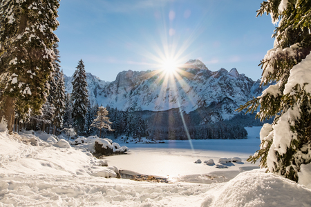 Mountain range Mangart seen from snow covert frozen lake Fusine with sunbeam Stock Photo