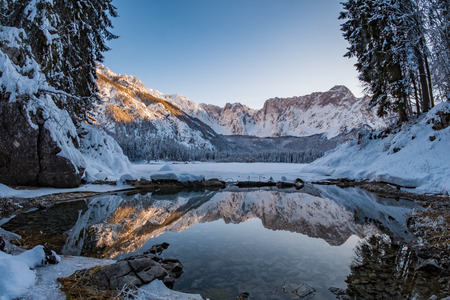 Mountain range Mangart reflecting in thawed part of lake Fusine in Italy Stock Photo