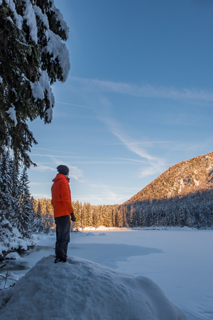 Man in orange jacket on small hill looking to frozen lake Fusine and sun covert forest