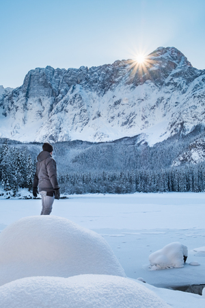 Man in grey jacket standing on snow covert lake Fusine and looking to mountain range Mangart in Italy
