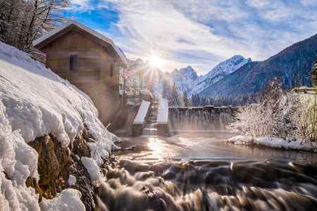 Water from lake Fusine flows over dam in river with mountain range Mangart and sunbeams in the background