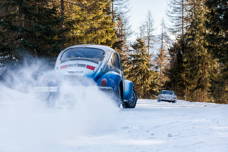 Vintage racing car drifting on a classic rally on snow covert road on mountain Planai  in Austria Stock Photo