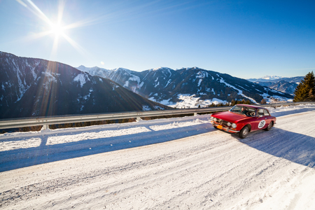 Red vintage racing car driving a classic rally on snow covert road on mountain Planai  in Austria Stock Photo