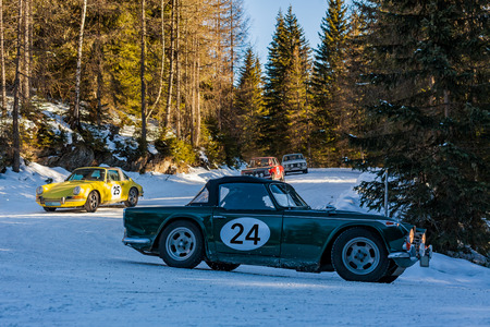 Vintage racing cars driving a classic rally on snow covert road on mountain Planai  in Austria