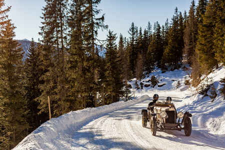 Vintage racing car driving a classic rally on snow covert road on mountain Planai  in Austria Stock fotó