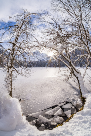 Broken ice on lake Fusine with mountain range Mangart and sunbeam in the background