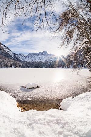 Mountain range Mangart seen from snow covert frozen lake Fusine with sunbeam Stock Photo