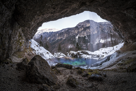 View from cave to waterfall Goriuda with turquoise lake in snow covered Italian aps