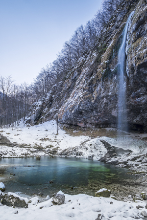 Solitude waterfall Goriuda flows in turquoise lake in snow covered Italian alps Stock Photo