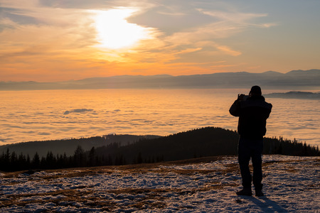 Man on snowy mountain Schoeckl taking photos of low stratus over city Graz and mountain Koralpe to sunset Stock Photo