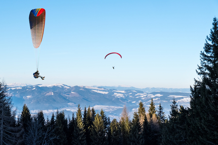 Two paraglider flying from mountain Schoeckl in winter over trees with nice panorama in Styria, Austria