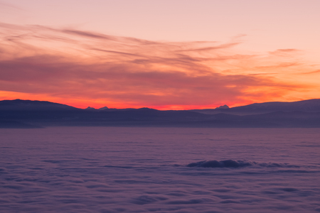 View from mountain Schoeckl in Styria over low stratus to mountain ranges Pack and Karawanks and Triglav to sunset