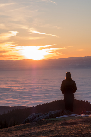 Woman standing on summit of mountain Schoeckl in Austria and looking over low stratus in city Graz to mountain Koralpe to sunset