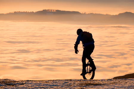 Man on unicycle riding on snowy mountain Schoeckl in Styria, Austria over low stratus fog to sunset Stock Photo