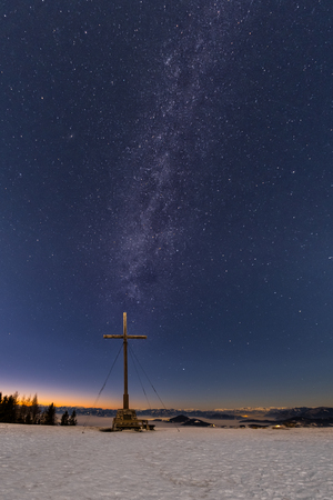 Milkyway over summit cross of snow covered mountain Schoeckl in Styria Austria
