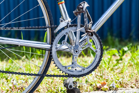 Chainring and chain with front derailleur, crank and pedals on vintage racing bicycle with crome frame