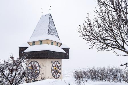 Snow covered Uhrturm clocktower landmark of city Graz on hill Schlossberg in winter Stock Photo