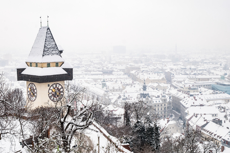 Snow covered Uhrturm clocktower landmark on hill Schlossberg with aerial view to city Graz in winter Stock Photo