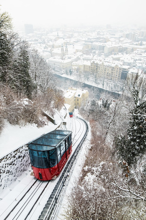 Red funicular railway cable car on hill Schlossberg with aerial view to snow covered city Graz in winter