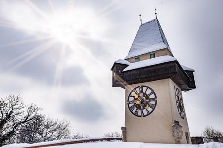 Sun flares over snow covered Uhrturm clocktower landmark of city Graz on hill Schlossberg in winter Stock Photo