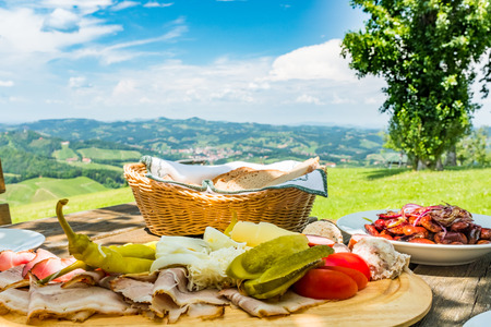 Brettljause with cold cuts, beans salad and bread on wooden table with beautiful view over green meadow to panoramic south styrian wine route