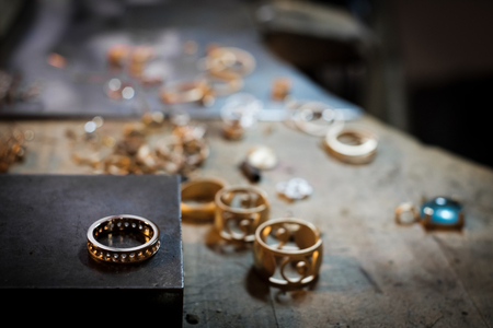 Gold ring on old workbench in an authentic jewelry workshop, in the background other gold jewelery for processing