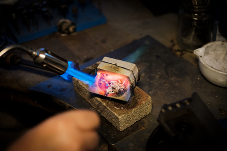 Jeweler melts with a flame silver or gold on old workbench in jewelers workshop