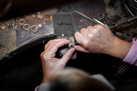 Un bijoutier polit une bague en or sur un vieil établi dans un authentique atelier de joaillerie Banque d'images
