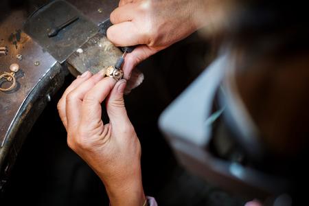 Juwelier poliert einen Goldring auf einer alten Werkbank in einer authentischen Schmuckwerkstatt Standard-Bild