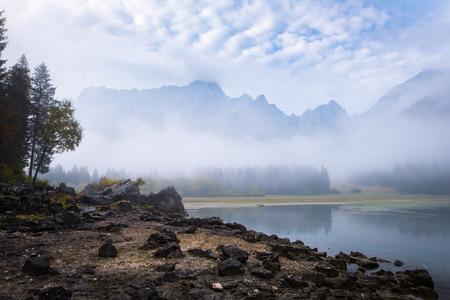 Beach with many rocks on lake Laghi di Fusine on a foggy morning with mountain range Mangart near Tarvisio in Italy, Europe 版權商用圖片