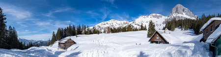 Panoramic view over snowy plateau Kaiserau with wooden huts to mountains Rottenmanner Tauern and Dachstein on a sunny winterday in Styria, Austria Stok Fotoğraf