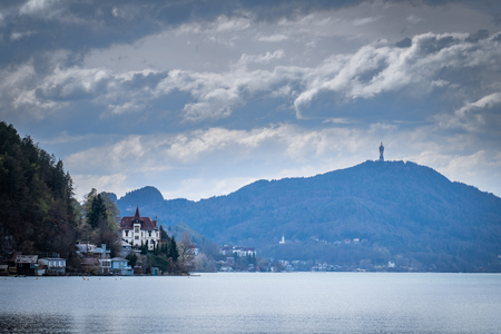 Panoramic view from beach Klagenfurt over lake Wörthersee through small village Maiernigg to mountain Pyramidenkogel with tower