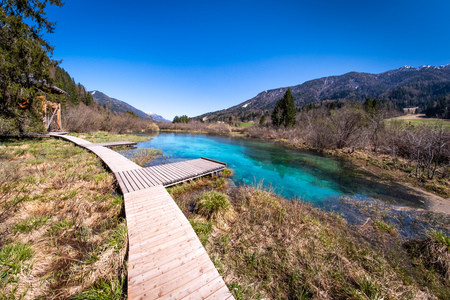 Lake Zelenci, source of the Sava Dolinka River, with the observation trail footbridge in nature reserve near the town of Kranjska Gora, in Slovenia