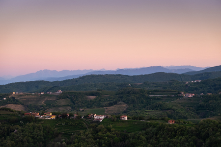 View from Gonjače Viewing Tower over the vineyard hills from village Vedrijan to sunrise over Julian Alps with mountain Matajur 免版税图像