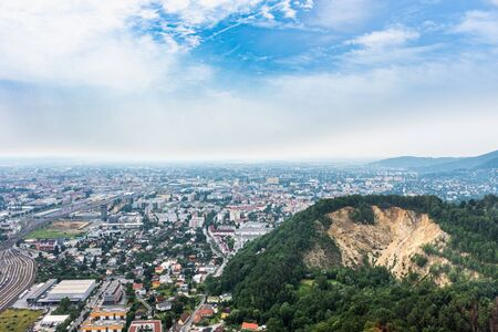 Aerial view of city Graz from helicopter drone with districts Gösting and Eggenberg and a quarry on a sunny summer day in Austria, Europe