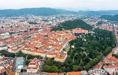 Aerial view of center city Graz from helicopter drone with hill Schloßberg, tower Uhrturm and central park on a cloudy summer day in Austria, Europe