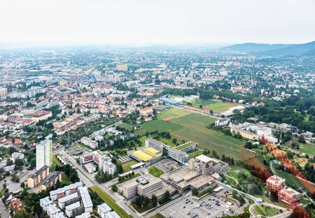 Aerial view of city Graz from helicopter drone with districts Gösting and the ukh hospital on a cloudy summer day in Austria, Europe